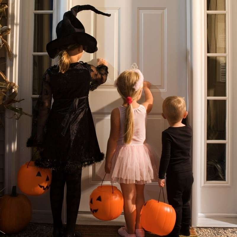 Three children of staggered heights wearing costumes and holding pumpkin buckets knock on a white door