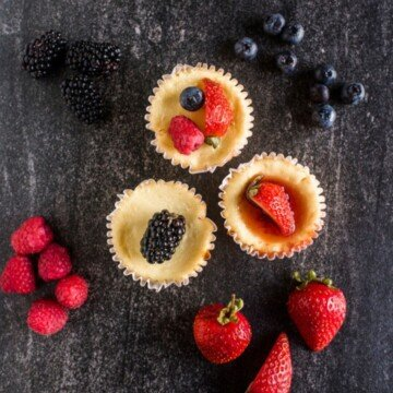 A black slate with three mini cheesecakes surrounded by raspberries, strawberries and blackberries