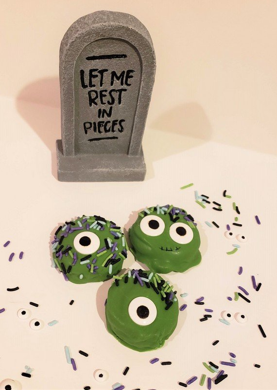 Green monster cookies with eyes and sprinkles for hair displayed beside a tombstone decoration for Halloween