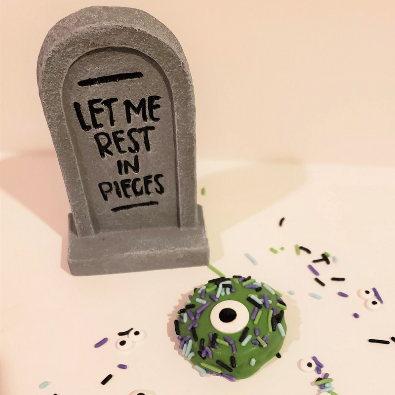 A green monster cookie with one candy eye displayed beside a decorative gravestone
