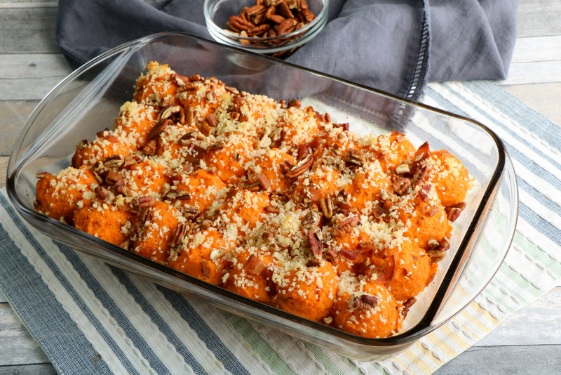 Sweet potato casserole in a transparent casserole dish on a blue and grey striped placemat with a blue napkin