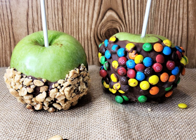 Two chocolate dipped Halloween apples, one with crushed nuts and the other with colorful button candies as decoration