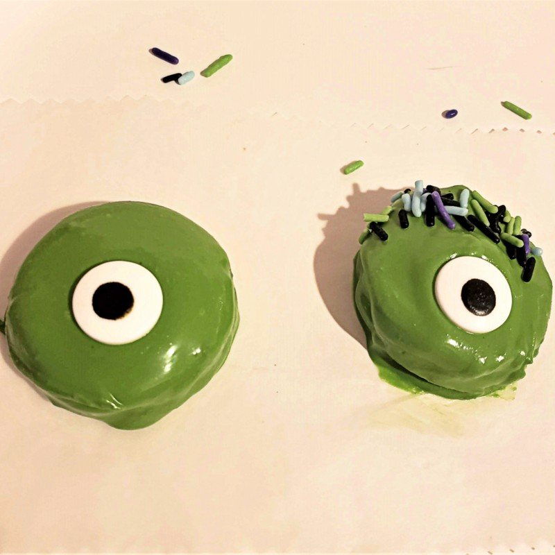 Two green chocolate covered cookies with candy eyes and one with purple, blue and black sprinkles as hair
