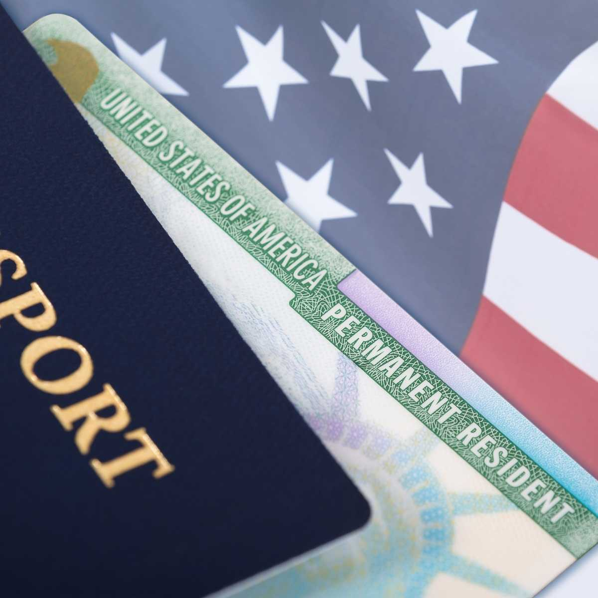 A green card or resident alien card with a US passport against a backdrop of the American flag