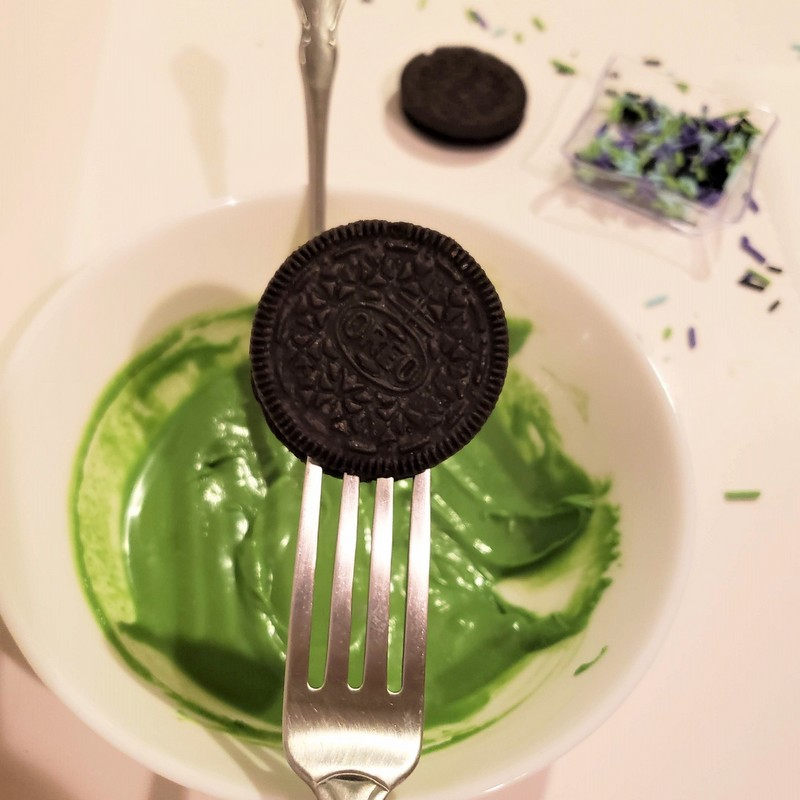 Dipping a chocolate sandwich cookie into a bowl of melted green candy melts using a fork