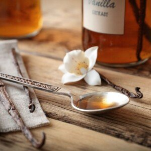 A teaspoon of vanilla extract on a chopping board with a vanilla pod and flour and a bottle of extract