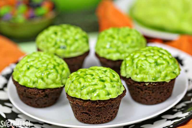 Five cupcakes on a plate with green icing that looks like green brains
