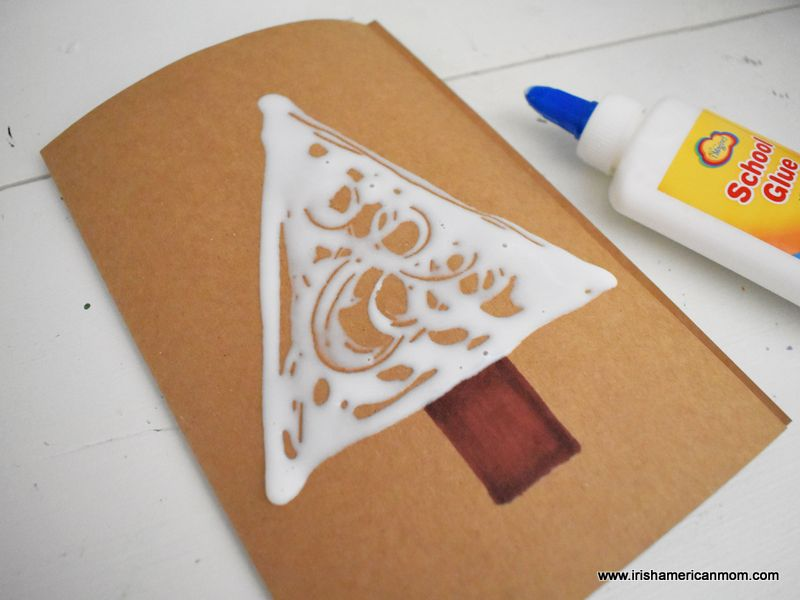 Brown card stock folded in half with the shape of a tree marked out with white glue