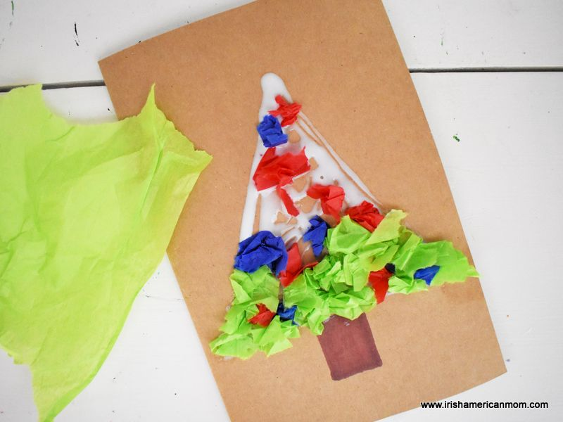 Green tissue paper beside a Christmas tree card craft