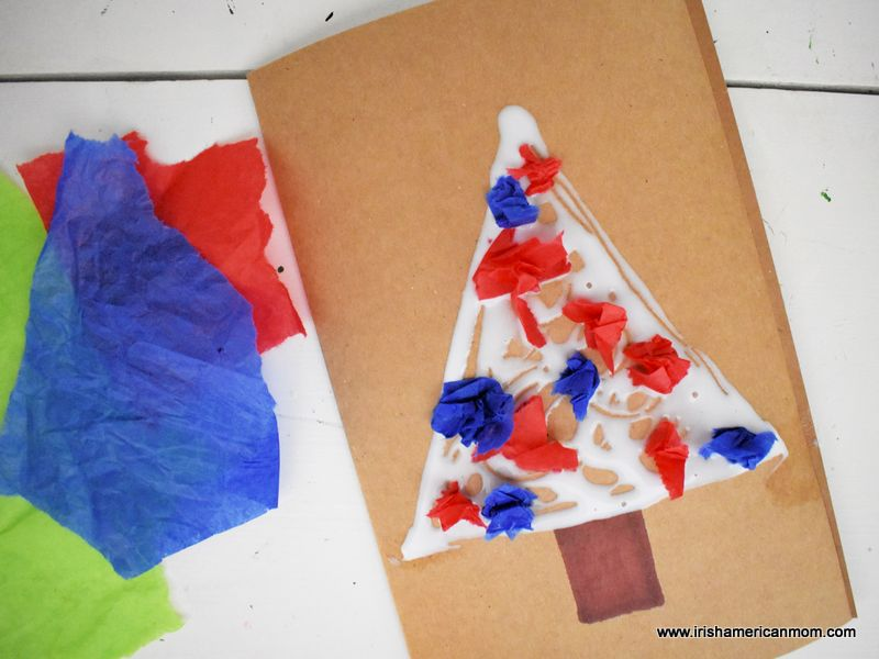 Red and blue crumpled pieces of tissue paper on a folded brown card to make a Christmas tree craft