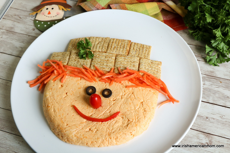 A circular cheese ball decorated as a scarecrow face served on a white plate beside a checkered napkin