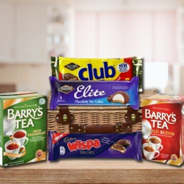 A gift basket on a table with boxes of tea bags and packets of biscuits or cookies