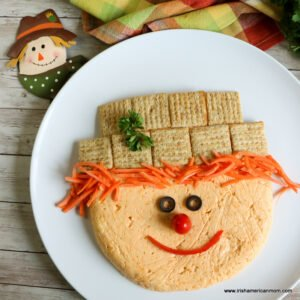 A scarecrow appetizer with an orange face made of cheese, matchstick carrot hair, a cracker hat, olive eyes, a tomato nose and a pepper strip mouth