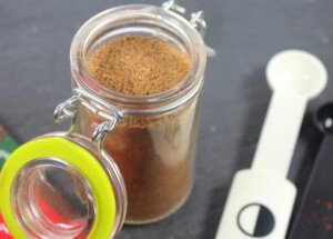 A brown spice blend in a small glass mason jar with a clip seal
