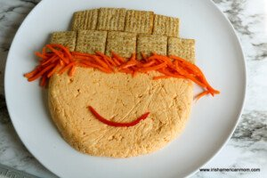 A scarecrow cheese appetizer on a plate with a slice of pepper as a mouth