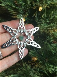 A silver star ornament with green central stone on a Christmas tree and being held in a person's hand
