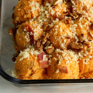 Close up view of a sweet potato casserole with pecan, bacon and panko topping