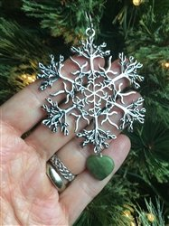 A hand raising a silver colored star pendant on a Christmas tree