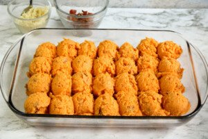Scoops of sweet potato mixture in a glass casserole on a marble counter