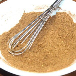 A balloon whisk in a bowl of brown spices