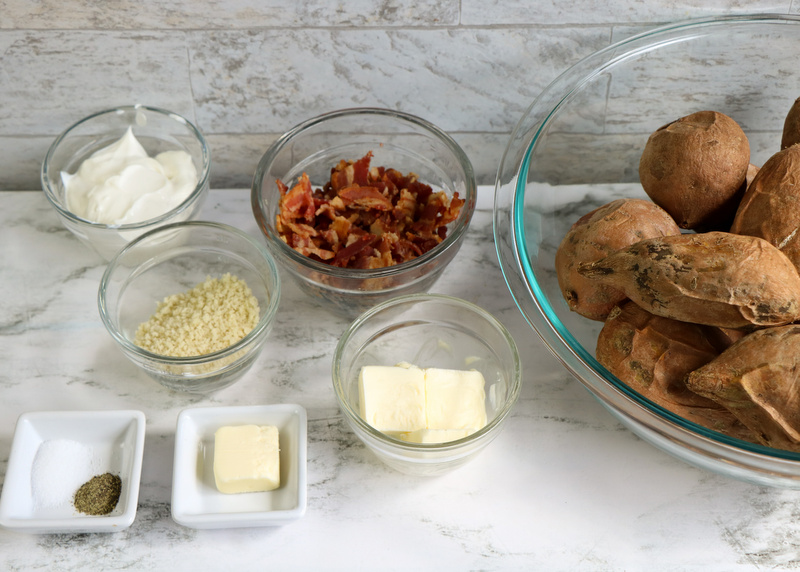 Baked sweet potatoes in a bowl beside bowls with sour cream pecans, panko, butter and salt and pepper