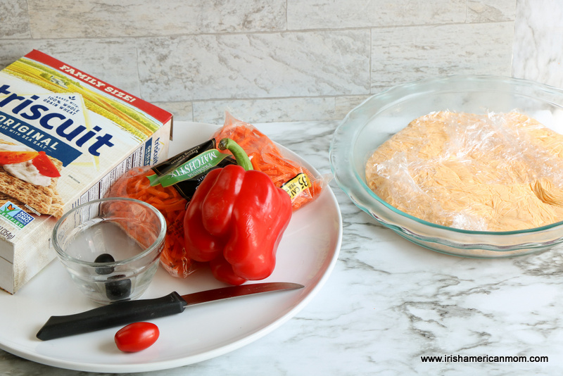 A white plate with a box of Triscuit crackers, carrots matchsticks, red pepper, olives, a cherry tomato and a knife beside a molded cheese disc