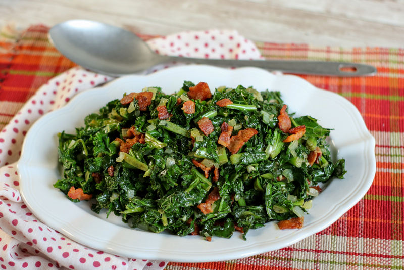 An oval white serving dish of kale with bacon bits on a plaid placemat with a silver spoon