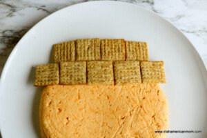 Two rows of wholewheat crackers forming a hat on a cheeseball