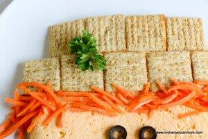 Carrot matchsticks under a cracker hat for a cheeseball appetizer