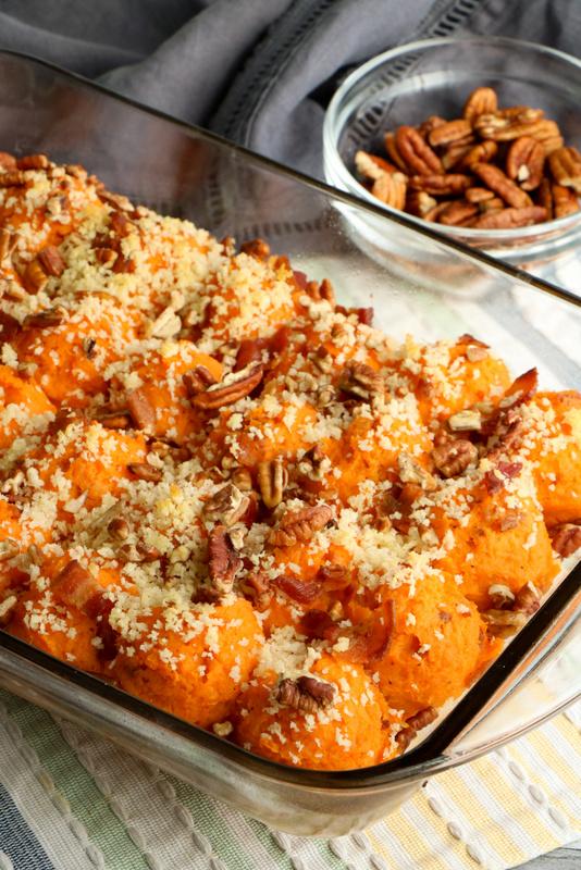 Pecan and panko topped sweet potato casserole in a glass casserole dish
