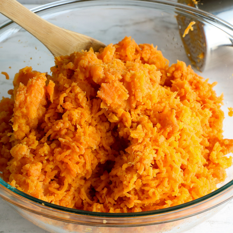 A glass bowl filled with sweet potato pulp with a wooden spoon and potato masher on a marble counter