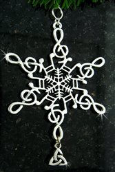 A silver snowflake ornament with music clef spokes and a trinity knot pendant