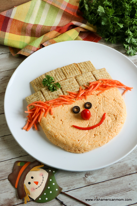 A cheese spread disc decorated as a scarecrow face for an edible appetizer