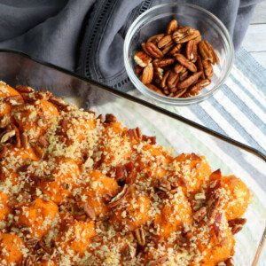Pecan topped sweet potato casserole in a glass dish beside a small bowl of pecans