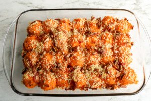 Mashed sweet potato in a casserole and topped with panko, bacon bits and chopped pecans