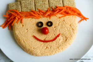 Olive eyes, tomato nose and pepper strip mouth on a cheese ball scarecrow face