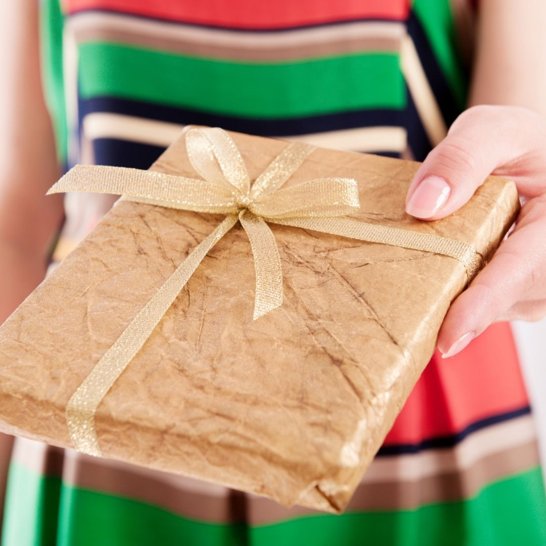 A book wrapped in brown paper with a bow held in a woman's hand