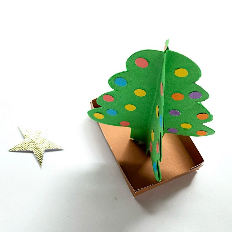 A green 3D paper Christmas tree on a brown box stand with a golden star lying beside it