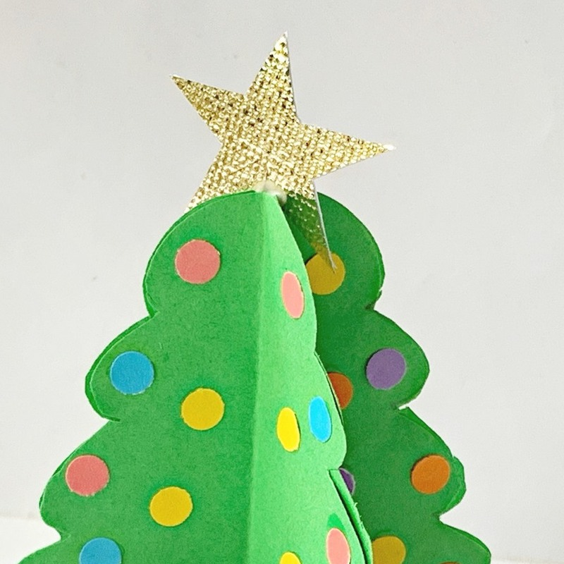 A star on top of a green paper Christmas tree