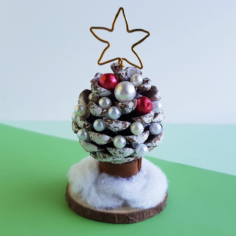 Pine cone ornament with bead decorations on a green surface