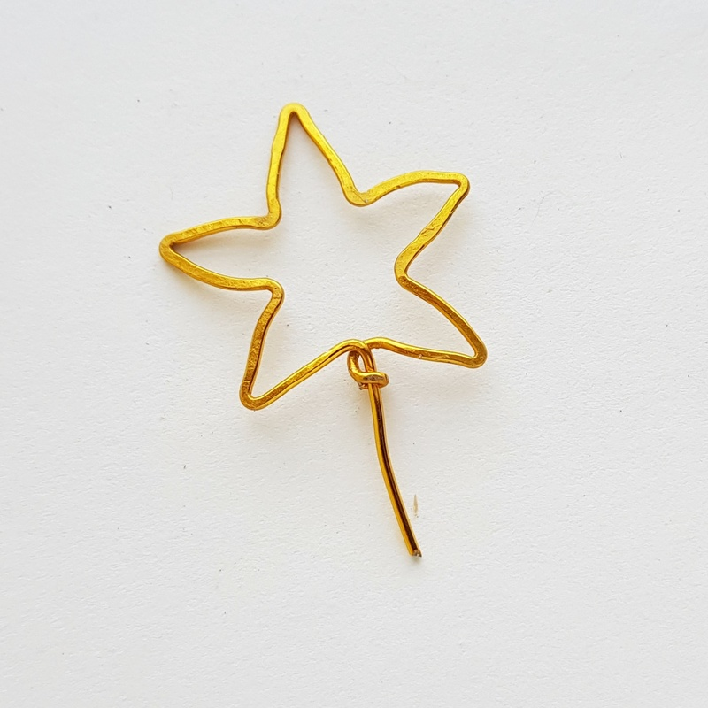 Golden wire star for craft projects on a white background