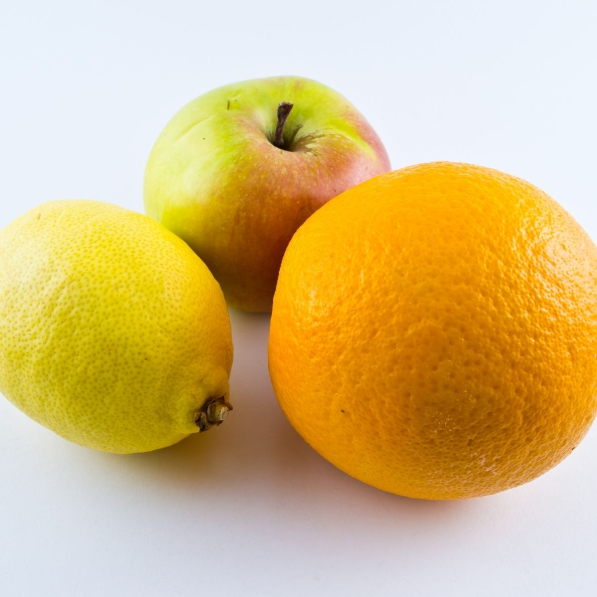An apple, an orange and a lemon on a white background