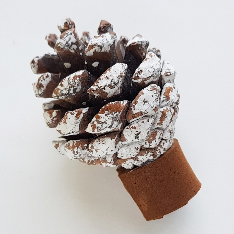 A pine cone with craft snow sprayed on it on top of a brown foam tree trunk