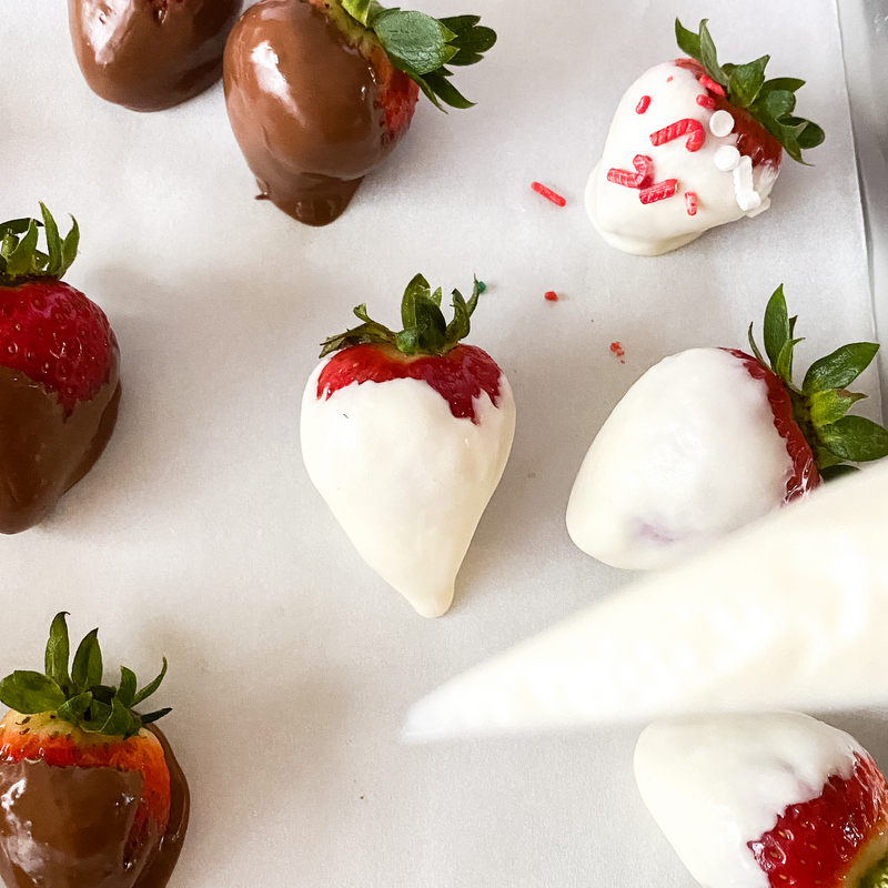 Melted white chocolate in a piping bag over chocolate covered strawberries