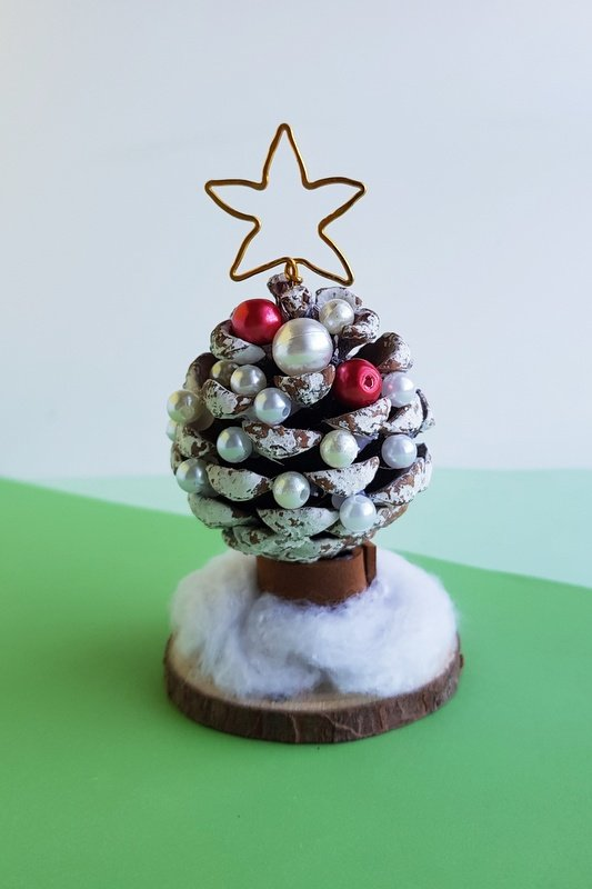 A pine cone with red and white beads and white paint to look like a Christmas tree displayed on a wooden disc