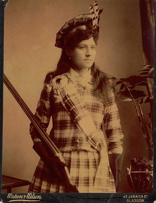 Black and white image of a woman wearing a tartan plaid suit while holding a rifle
