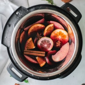 Sliced fruit, cinnamon stick and star anise in red wine in a pot