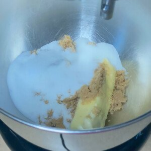 White sugar, brown sugar and a stick of butter in a silver bowl