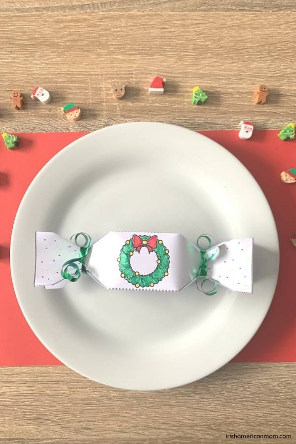 A hand colored paper Christmas cracker on a white plate and red placemat