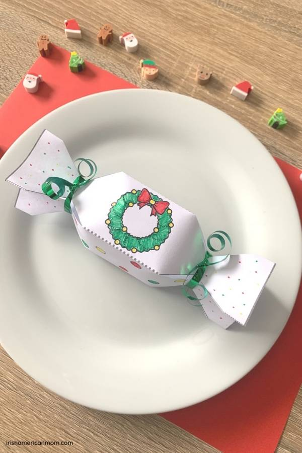 A paper Christmas cracker on a white plate